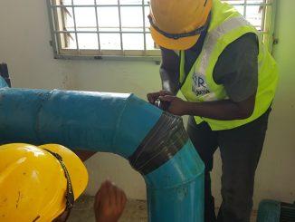 Waterproof pipe repair tape being applied to seal a leaking pipe